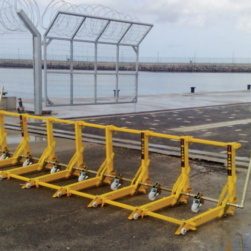 Yellow portable vehicle barrier in front of a gate leading to the wharf