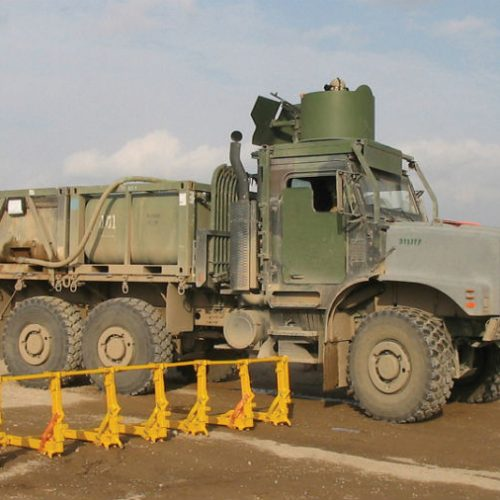 Military trucks near the vehicle barrier