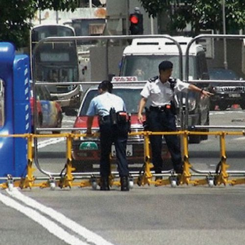 Police personnel securing the entrance to a military base using the modular vehicle barrier